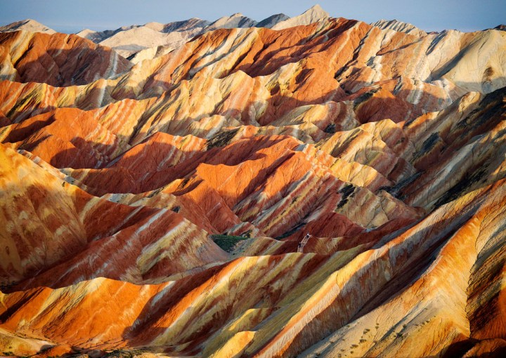 """Two tourists (lower right)among the vivid ZhangyeLandformsin central China. The banding of the rocks isthe result of red sandstone and mineral deposits being laid down over 24 million years &the whole """"layer cake"""" then being upturned by seismic churning. Click  here for full gallery."""