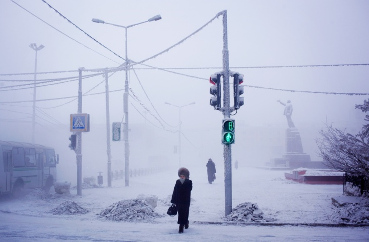 A woman hurries through the fog which lingers through the coldest weeks in Yakutsk.  In background a statue of Lenin presides over the central square of the city.