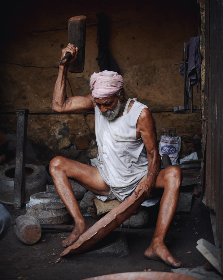 "For 61 years he's sat here, legs dwindling to sticks as he thumps cooking pots into shape. His sons work beside him, three hammer blows occasionally falling together in synch, then scattering again into the random beat of the workshop.  I ask whether the girls admired his arms when he was young but he scolds me for rudeness. He's more comfortable talking about the men with firebombs who drove his family out of their homeland. His father had made the decision to stay when Pakistan was formed around them, a Sikh clan in a new Muslim nation, but eventually the mob violence visited their neighbourhood and they fled.  Like so many who've lived through big history he's nostalgic for the past. ""Under the British we felt enormous pressure but we were innocent then. Now the people have freedom but we no longer love each other.""  But his old-testament face lights up when his grandchildren appear, they're educated and will live a different life. He props a favourite onto his knee, ""these little ones can choose their own lives and of course I'm happy for that"".  Finally, after the curious crowd have drifted away from us he leans in close, ""you asked about my arms? My wife told me she always felt safe in these arms"". He rocks back and sweeps a hand over his children, his workshop, his little empire, ""and she was, she always was"""
