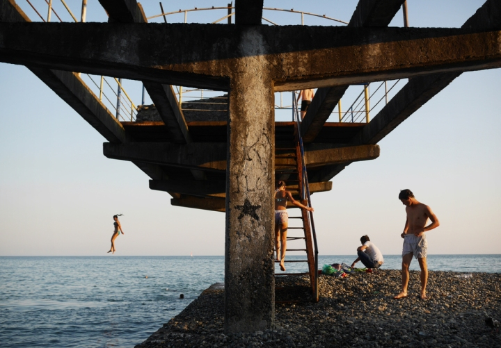 """Locals on a ruined pier in Abkhazia, a breakaway republic caught between Russian and Georgian geopoliticalambitions. Pre-war Abkhazia accounted for most of Georgia's coastline and was famous as the Soviet Union's """"Red Riviera"""". Following the war, international sanctions and a naval blockade devastated the region's economy. Today it is a contrast of natural beauty and ravaged infrastructure."""