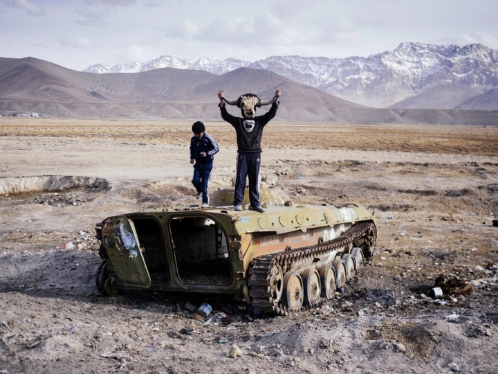 """Twoboys playing on the shell of a Soviet APC in Murghab, the highest town in Tajikistan. Built by the Russians in the late 19th century, Murghab served as a staging post for the cloak & dagger activities of their operatives during the clash of empires known to the British as """"The Great Game"""" and to the Russians as """"The Tournament of Shadows""""."""